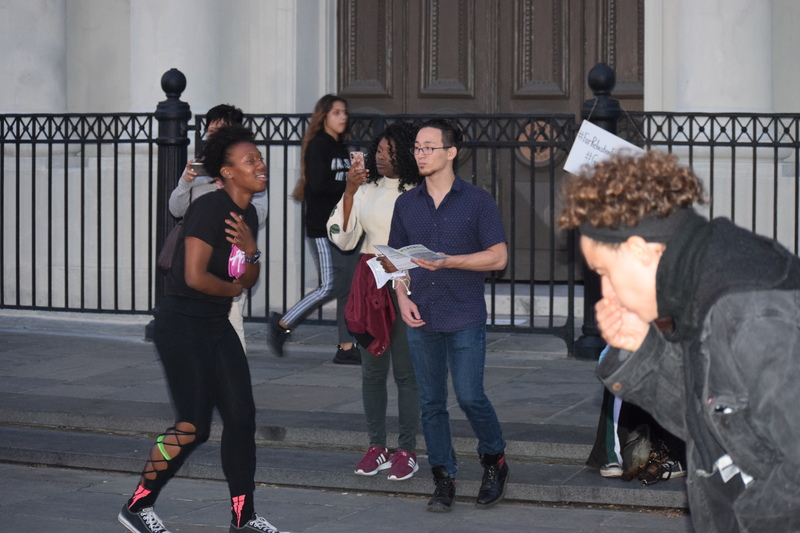 """Activists perform stage """"Asphyxiated: Exposing Gordon Plaza"""" in front of St. Louis Cathedral."""